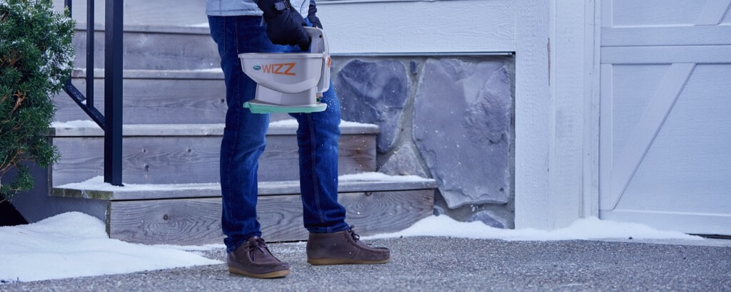 Person applying Scotts Ice Melt with Scotts Wizz Handheld Spreader