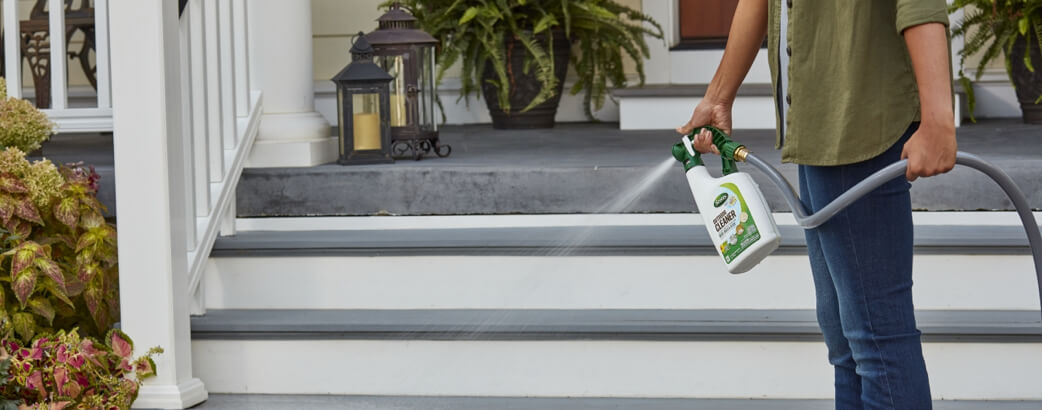 Person cleaning front porch with Scotts Ourdoor Cleaner with Oxiclean