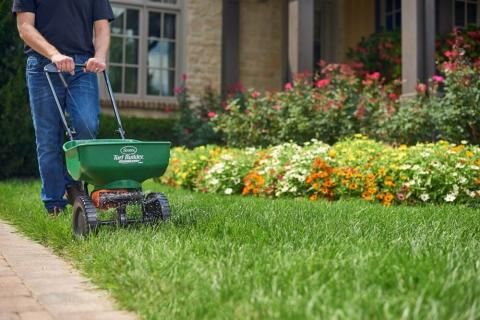 Man using a broadcast spreader with edge guard technology fertilizing a well-maintained lawn.