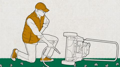 Illustration of a man connecting hose to a lawnmower for cleaning.