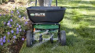 A Scotts Elite fertilizer spreader sitting on a green lawn.