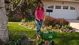 Lady in Lawn using Spreader - How to Find Your Scotts® Spreader Settings