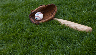 Baseball in a baseball glove next to a bat on a green lawn.