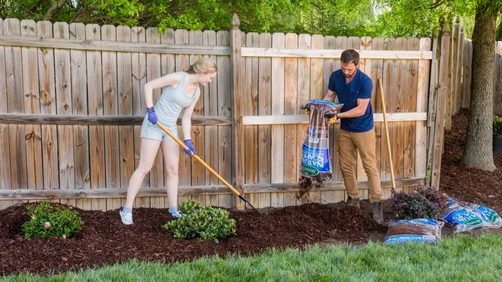 Genial Benefits Of Mulching: Couple Spreading New Mulch In Bed Near Fence