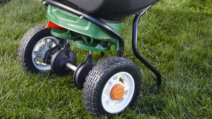 A fertilizer spreader sitting on a green lawn.