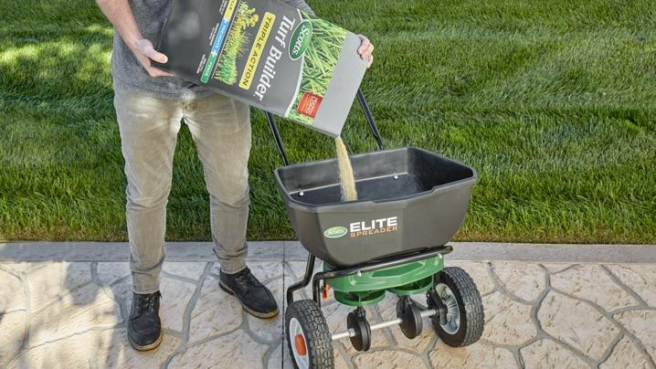 Man pouring Triple Action into Elite spreader