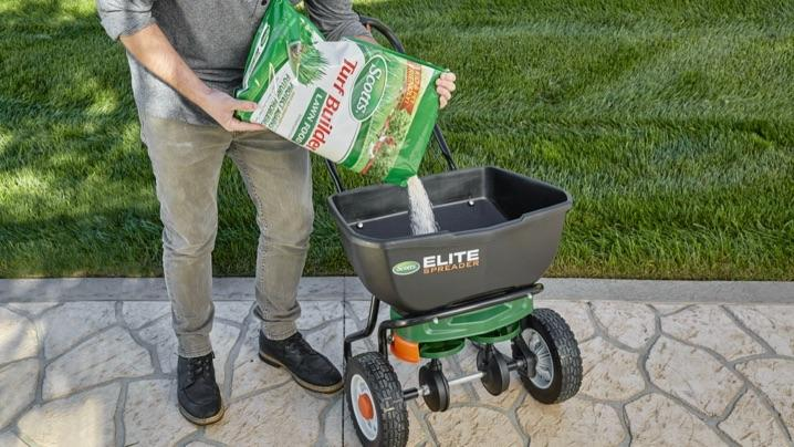 A man pouring Scotts® Turf Builder Lawn Food into spreader.
