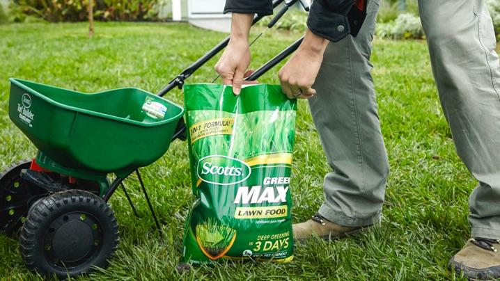 Man loading Scotts® Green Max™ Lawn Food into spreader