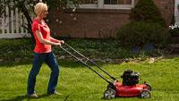 Woman pushing red lawn mower cutting a green lawn.