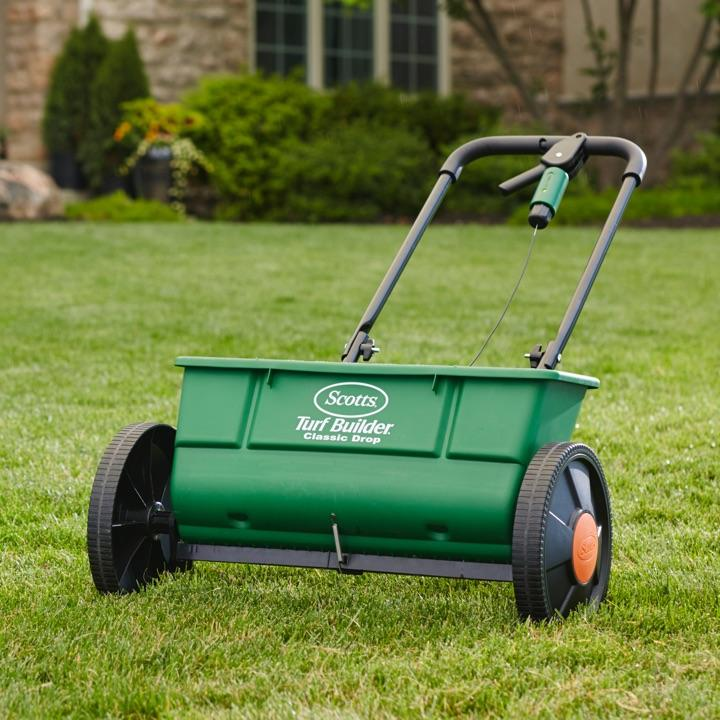 Scotts® Turf Builder® Classic Drop Spreader on a green lawn.