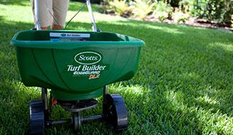 A Scotts fertilizer spreader sitting on a green lawn.