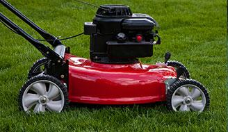 Red lawnmower sitting on a green lawn.