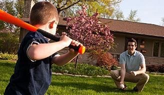 Father and son playing baseball on a green lawn.