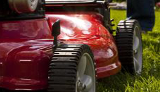 Red lawnmower sitting on a grass lawn.