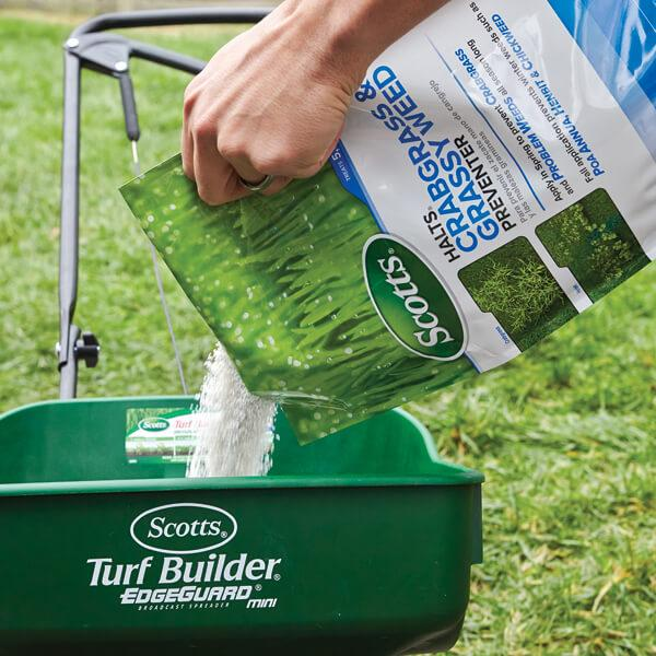 Image of a person pouring a bag of Scotts® Halts® Crabgrass & Grassy Weed Preventer into a spreader preparing for use