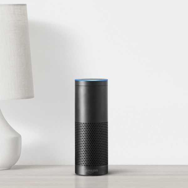 Alexa console sitting on white table next to white lamp