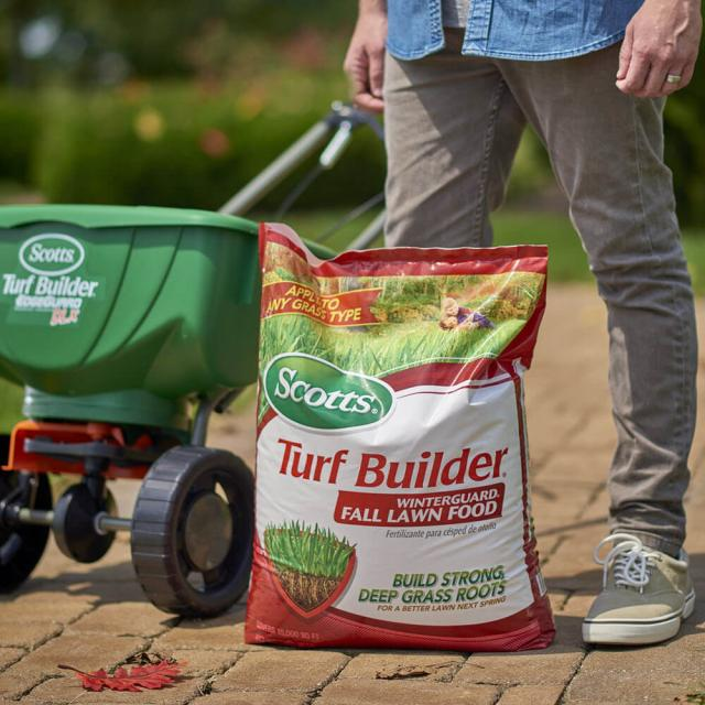 User standing in front of a bag of Scotts® Turf Builder® WinterGuard® Fall Lawn Food