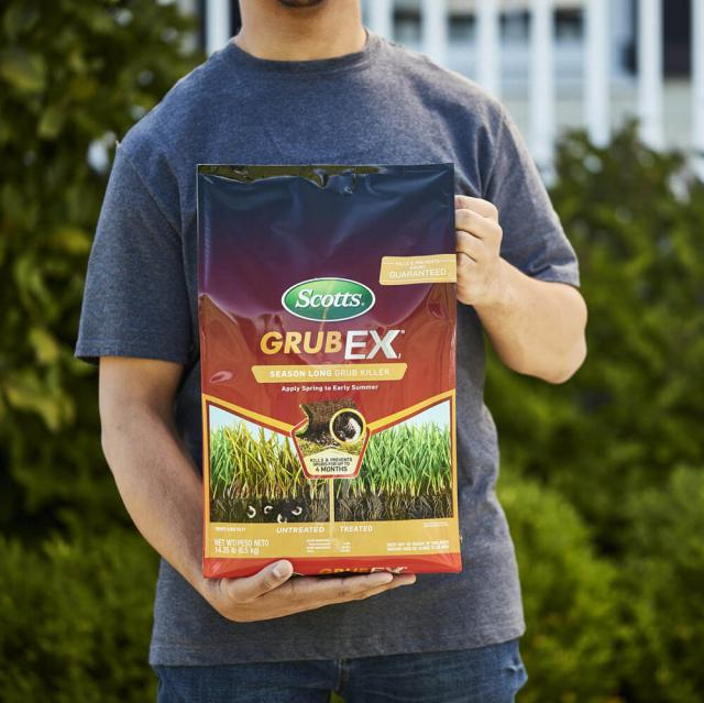 Man holding a bag of Scotts GrubEx