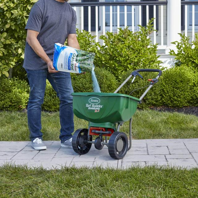Man pouring Scotts Turf Builder Grass Seed Sun & Shade Mix in a spreader