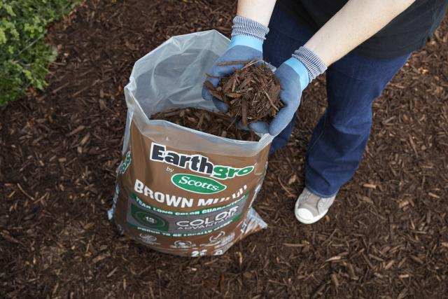 Consumer removing brown mulch from packaging to use on lawn