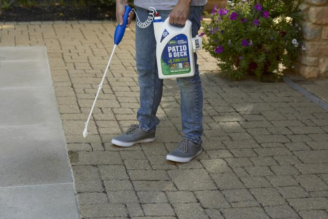 Man using Scotts® Outdoor Cleaner Patio & Deck With ZeroScrub™ Technology to clean a patio.