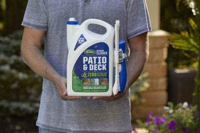 Man holding Scotts® Outdoor Cleaner Patio & Deck With ZeroScrub™ Technology.