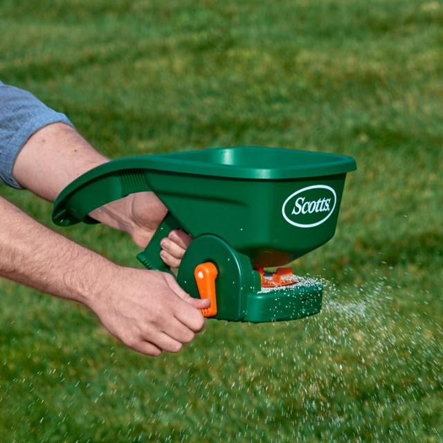 User spreading fertilizer on lawn with product